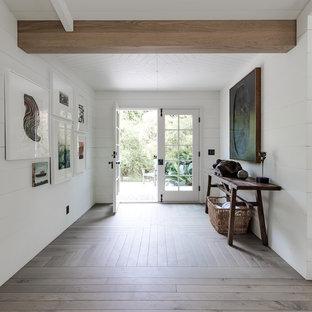 Foto på en mellanstor maritim foajé, med vita väggar, en dubbeldörr, en vit dörr, mellanmörkt trägolv och brunt golv