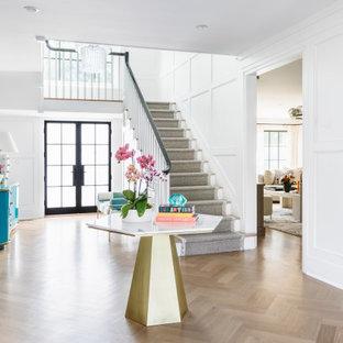 Foto di un ingresso contemporaneo con pareti bianche, pavimento in legno massello medio, una porta a due ante, una porta in vetro, pavimento marrone e pannellatura
