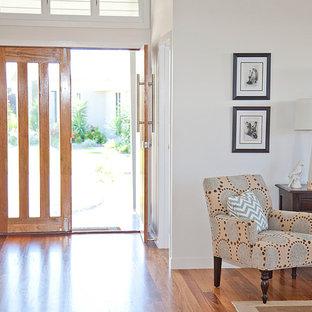 Imagen de entrada costera con suelo de madera en tonos medios y puerta doble