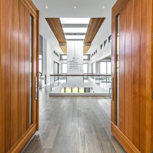 Entryway - large contemporary light wood floor and brown floor entryway idea in Seattle with white walls and a dark wood front door