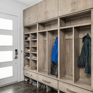 На фото: тамбур среднего размера в современном стиле с белыми стенами, полом из керамогранита, одностворчатой входной дверью, белой входной дверью и коричневым полом