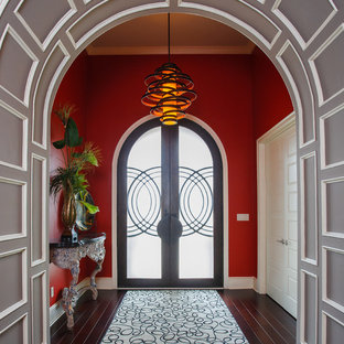 Mid-sized trendy dark wood floor and brown floor entryway photo in Little Rock with red walls and a glass front door