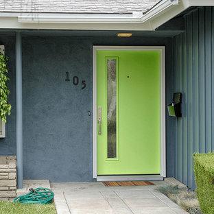 Immagine di una grande porta d'ingresso design con pareti blu, una porta singola e una porta verde