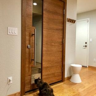 Foto på en mellanstor funkis ingång och ytterdörr, med beige väggar, ljust trägolv, en enkeldörr och gult golv