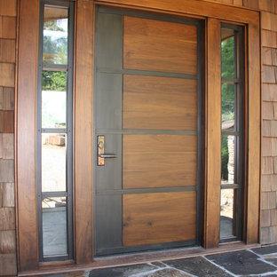 Cette image montre une grand porte d'entrée minimaliste avec un mur marron, un sol en ardoise, une porte simple et une porte marron.