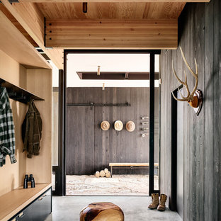 Example of a country entryway design in Other with black walls and a glass front door