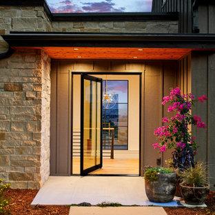 Lantlig inredning av en mellanstor ingång och ytterdörr, med vita väggar, mellanmörkt trägolv, en pivotdörr, glasdörr och brunt golv