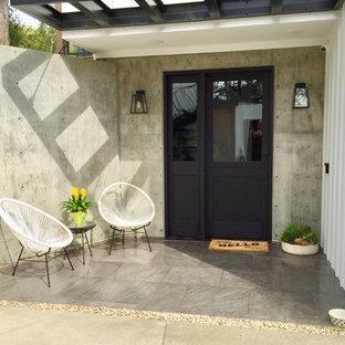 Example Of A Trendy Gray Floor Entryway Design With A Black Front Door And  Gray Walls