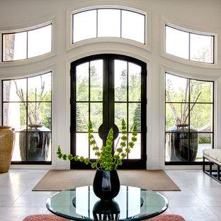 Idée de décoration pour un très grand hall d'entrée design avec une porte double, une porte en verre, un mur blanc, un sol en carrelage de céramique et un sol beige.