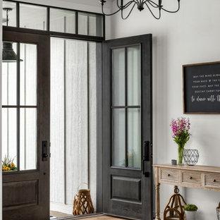 На фото: входная дверь среднего размера в стиле кантри с белыми стенами, светлым паркетным полом, двустворчатой входной дверью, серой входной дверью и сводчатым потолком