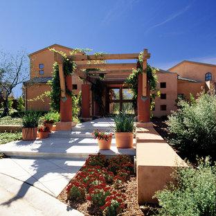 Exemple d'une grand porte d'entrée sud-ouest américain avec un mur orange et une porte en verre.