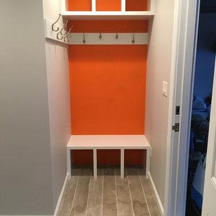 Idées déco pour une petit entrée contemporaine avec un vestiaire, un mur orange et un sol en carrelage de porcelaine.