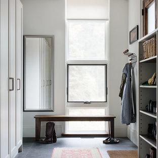 トロントの広い片開きドアコンテンポラリースタイルのおしゃれなマッドルーム (白い壁、御影石の床、木目調のドア) の写真