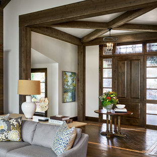 ポートランドの大きい片開きドアカントリー風おしゃれな玄関ロビー (ライムストーンの床、濃色木目調のドア、茶色い床、白い壁) の写真