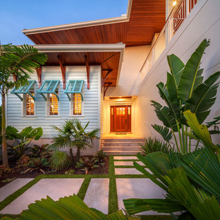 Inspiration for a beach style front door remodel in Tampa with white walls and a medium wood front door