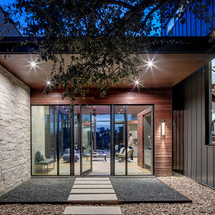 Inspiration for a contemporary front door in Austin with a pivot front door and a glass front door.