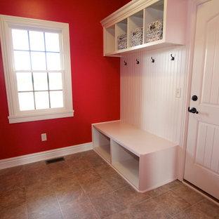 他の地域の広い片開きドアおしゃれなマッドルーム (赤い壁、クッションフロア、白いドア) の写真
