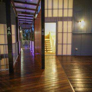 Mid-sized trendy dark wood floor entryway photo in Sunshine Coast with metallic walls and a glass front door