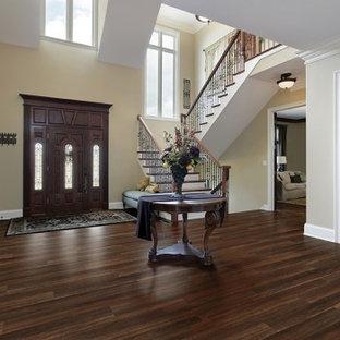 サクラメントの大きい片開きドアヴィクトリアン調のおしゃれな玄関ロビー (クッションフロア、ベージュの壁、濃色木目調のドア、茶色い床) の写真