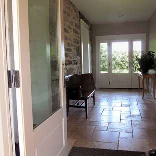 Example of a mid-sized country limestone floor entryway design in Toronto with beige walls and a white front door