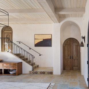 Foto de distribuidor mediterráneo, grande, con paredes blancas, suelo de piedra caliza, puerta doble, puerta de madera oscura y suelo beige