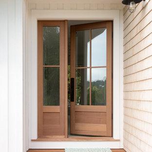 ポートランド(メイン)の片開きドアトラディショナルスタイルのおしゃれな玄関ドア (白い壁、塗装フローリング、淡色木目調のドア) の写真