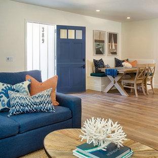 Entryway - large contemporary medium tone wood floor and brown floor entryway idea in Orange County with beige walls and a blue front door