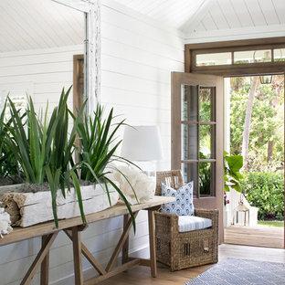 Modelo de entrada costera con paredes blancas, suelo de madera en tonos medios, suelo marrón, puerta simple y puerta de madera en tonos medios