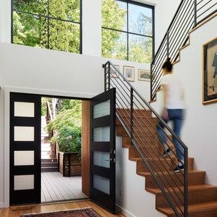 Idéer för mellanstora funkis ingångspartier, med vita väggar, mellanmörkt trägolv, en dubbeldörr och en svart dörr