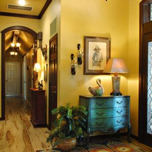 Foto di un grande ingresso stile americano con pareti gialle, parquet chiaro, una porta singola e una porta in legno scuro