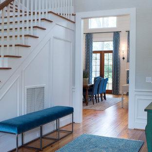 Réalisation d'une grande porte d'entrée tradition avec un mur beige, un sol en bois brun, une porte simple, une porte marron et un sol marron.