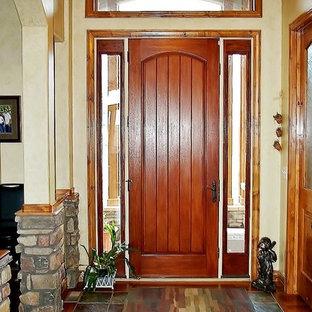Idées déco pour un hall d'entrée craftsman de taille moyenne avec un sol en ardoise, une porte simple, une porte en bois brun, un mur beige, un sol multicolore et un plafond voûté.