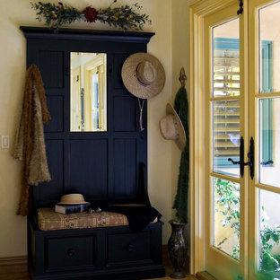 Foto di un corridoio tradizionale di medie dimensioni con pareti gialle, pavimento in legno massello medio, una porta a due ante, una porta gialla e pavimento marrone