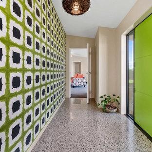 Immagine di una porta d'ingresso minimal con pavimento in cemento, una porta verde e una porta singola