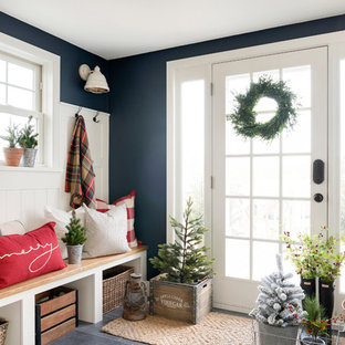 Mid-sized country mudroom in Minneapolis with blue walls, a single front door, grey floor and a glass front door.