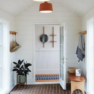 Imagen de vestíbulo costero con paredes blancas, suelo de ladrillo, puerta simple y puerta de vidrio