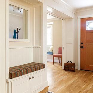 Aménagement d'une entrée craftsman de taille moyenne avec un vestiaire, un mur beige, un sol en bois brun, une porte simple, une porte en bois brun et un sol marron.