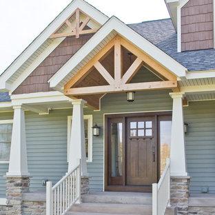 クリーブランドの片開きドアトラディショナルスタイルのおしゃれな玄関ドア (緑の壁、コンクリートの床、濃色木目調のドア、グレーの床) の写真