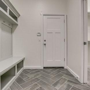 Ejemplo de vestíbulo posterior de estilo americano, de tamaño medio, con paredes grises, puerta simple, puerta blanca, suelo de baldosas de cerámica y suelo negro
