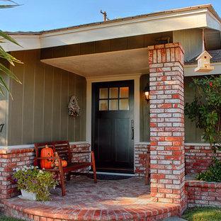Стильный дизайн: входная дверь среднего размера в стиле кантри с оранжевыми стенами, одностворчатой входной дверью и черной входной дверью - последний тренд