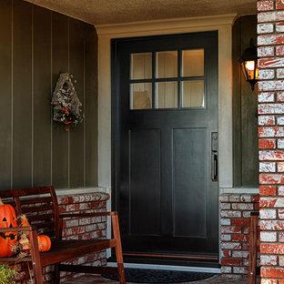 Modelo de puerta principal de estilo americano, de tamaño medio, con parades naranjas, puerta simple y puerta negra