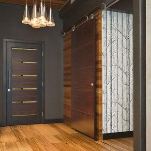ポートランドの片開きドアコンテンポラリースタイルのおしゃれな玄関 (黒い壁、無垢フローリング) の写真