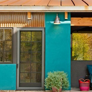 Inspiration for a southwestern entryway remodel in Denver with a glass front door