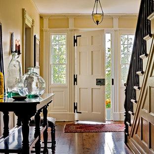 Cette image montre un hall d'entrée traditionnel avec un mur jaune, une porte simple et une porte blanche.