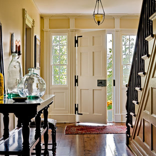 Example of a classic entryway design in New York with yellow walls and a white front door