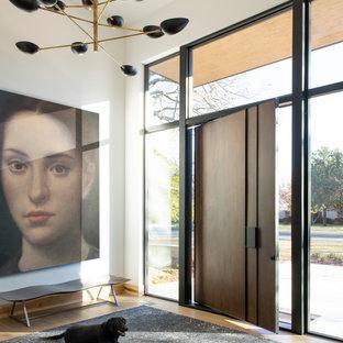 ダラスの広い回転式ドアコンテンポラリースタイルのおしゃれな玄関ロビー (白い壁、無垢フローリング、濃色木目調のドア、茶色い床) の写真