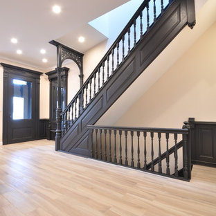 Inspiration for a mid-sized victorian light wood floor entryway remodel in New York with beige walls and a black front door