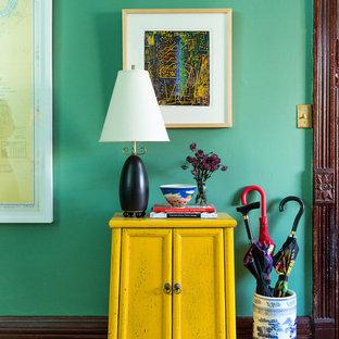 Idée de décoration pour une entrée bohème avec un mur vert et un sol en bois clair.