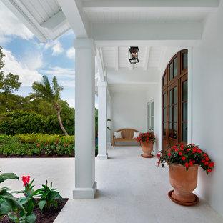 他の地域の広い片開きドアビーチスタイルのおしゃれな玄関ドア (白い壁、トラバーチンの床、濃色木目調のドア、ベージュの床) の写真