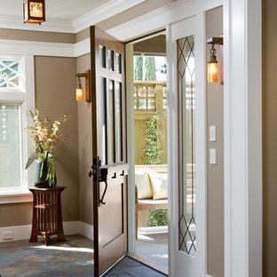 Ispirazione per un ingresso o corridoio american style con pareti marroni, pavimento in ardesia, una porta in legno scuro e una porta singola